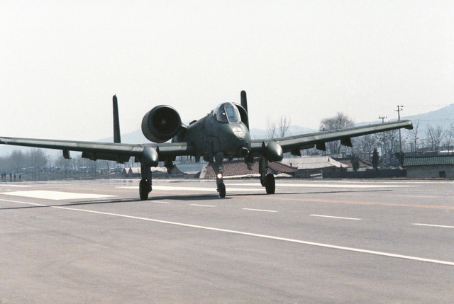 A US Air Force A-10A Thunderbolt II aircraft lands on a highway during the joint US and South Korean Exercise TEAM SPIRIT '86. The highway is being used by various aircraft for emergency landing training