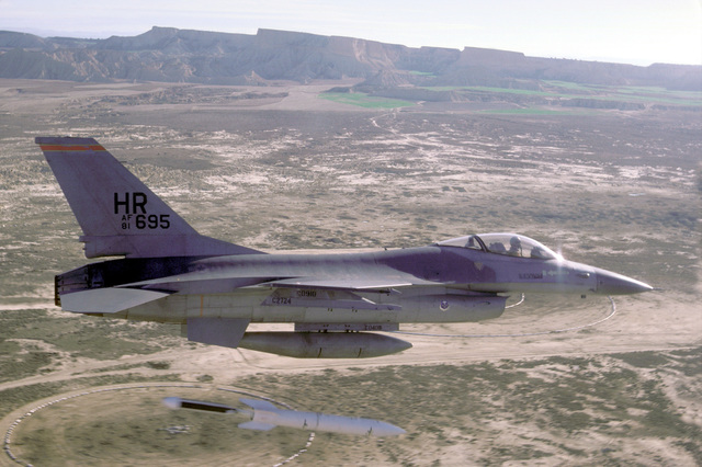 An air-to-air right side view of a 313th Tactical Fighter Squadron F-16A Fighting Falcon aircraft dropping a BDU-38 nuclear simulator while participating in a bombing practice exercise over the Spanish-American Bardenas Bombing Range