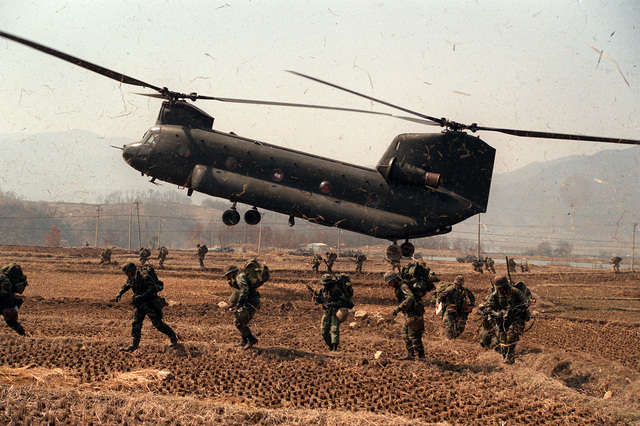 Soldiers of the 1ST Bn., 35th Inf., 25th Inf. Div., move out of the air assault landing zone after being dropped off by a CH-47 Chinook helicopter during the joint U.S./Korean Exercise Team Spirit '86