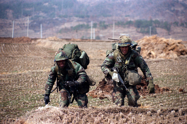 The platoon sergeant and radio-telephone operator of the 1ST Bn., 35th Inf., 25th Inf Div., move out from the landing zone while participating in an air assault during the joint U.S./Korean Exercise Team Spirit '86