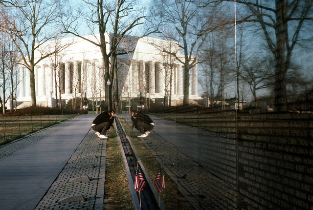 A visitor studies names on the Vietman Memorial Wall with the Lincoln Memorial reflected on the wall and seen in the background. Exact Date Shot Unknown