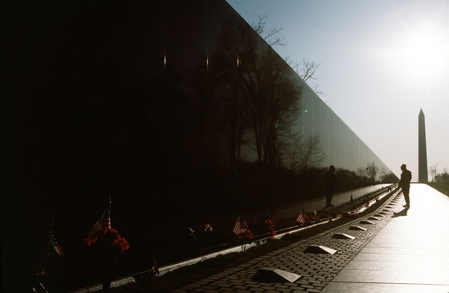A visitor studies names on the Vietman Memorial Wall with the Washington Memorial in the background. Exact Date Shot Unknown