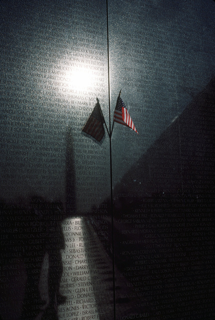 An American Flag stuck between two sections of the Vietnam Wall memorial. The Washington Memorial is reflected among the names of casualties of the war. Exact Date Shot Unknown