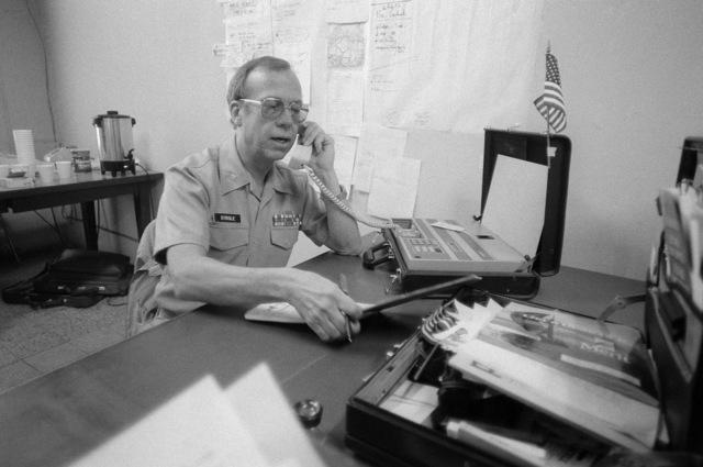Captain (CAPT) Douglas L. Strole talks from a briefcase telephone