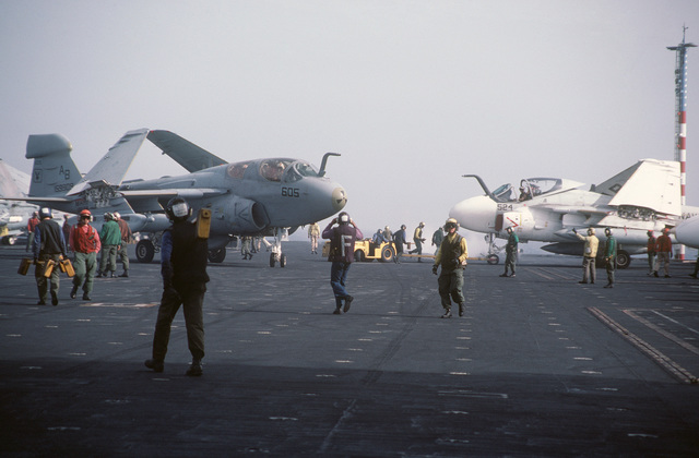 Crew members of the aircraft carrier USS AMERICA (CV 66) carry out flight deck operations. An A-6E Intruder aircraft, right, and EA-6B Prowler aircraft, left, are in the background