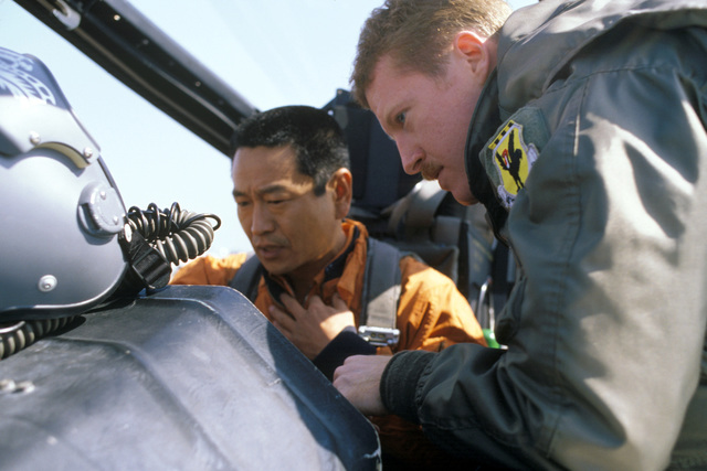 A US Air Force pilot explains the cockpit of an F-15 Eagle aircraft to a Japanese Air Self Defense Force pilot during the joint US Japanese Exercise COPE NORTH '86-3