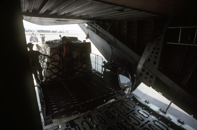 A cargo trailer loaded with pallets containing humanitarian assistance supplies is unloaded from a C141B Starlifter aircraft from the 14th Military Airlift Squadron.  The supplies were donated to Hondurans by private relief agencies in the United States