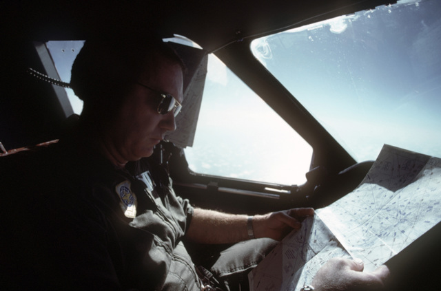 Lieutenant Colonel (LTC) Curtis K. Maloy, 14th Military Airlift Squadron, examines his flight plan from the cockpit of a C141B Starlifter aircraft while en route to Honduras.  The aircraft is carrying humanitarian assistance supplies donated by private relief agencies in the United States