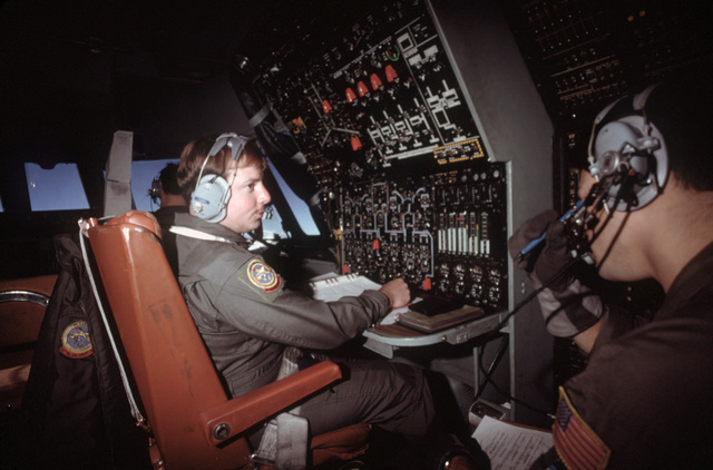 Sergeant (SGT) Gerald W. Kadolph, 14th Military Airlift Squadron, works at his station aboard a C141B Starlifter aircraft en route to Honduras.  The aircraft is carrying humanitarian assistance supplies donated by private relief agencies in the United States