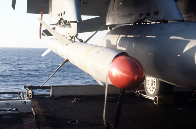 An AGM-88A high-speed anti-radiation missile mounted on the wing pylon of an F/A-18A Hornet aircraft parked aboard the aircraft carrier USS CORAL SEA (CV 43). The aircraft is being prepared for a air strike on targets in Libya