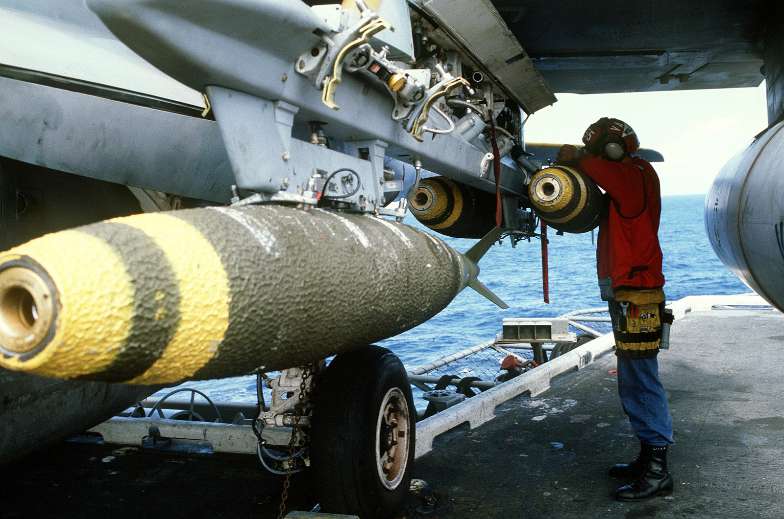An aviation ordnanceman aboard the aircraft carrier USS CORAL SEA (CV-43) checks the connections on Mark 82 500-pound bombs mounted on an A-6E Intruder aircraft prior to an air strike on targets in Libya