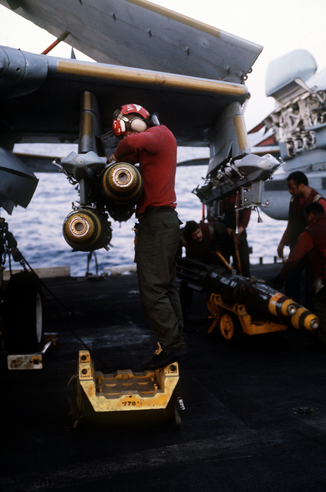 Aviation ordnancemen aboard the aircraft carrier USS CORAL SEA (CV-43) load Mark 82 500-pound bombs on an A-6E Intruder aircraft prior to an air strike on targets in Libya