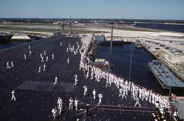 Crewmen aboard the aircraft carrier USS SARATOGA (CV 60) gathers near the starboard rail as the ship approaches the dock. The ship is returning to port after a deployment to the Mediterranean Sea