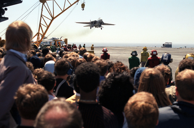 Visitors observe from the flight deck as an F-14A Tomcat aircraft approaches for a landing aboard the nuclear-powered aircraft carrier USS CARL VINSON (CVN 70) during a dependent's day cruise