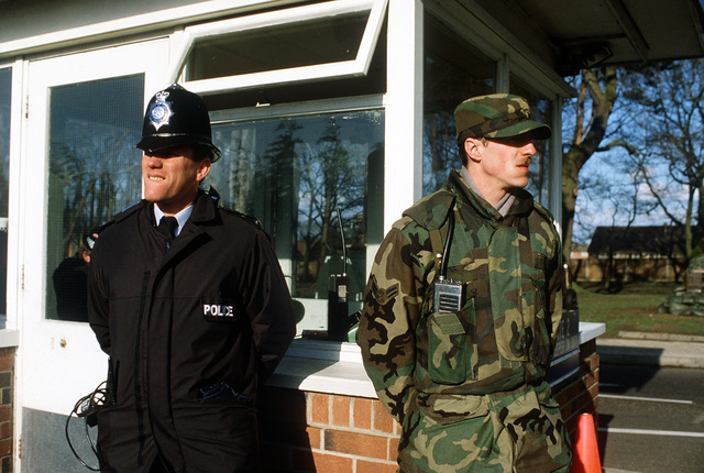 AIRMAN 1ST Class Douglas de Castro, 7348th Security Police Squadron, stands guard with a British policeman at the Lords Walk Gate. Approximately 1,000 demonstrators are protesting the base's participation in the U.S. bombing of Libya last week. The base is temporarily closed while military and Suffolk County police secure the outer perimeter of the base and escort protesters