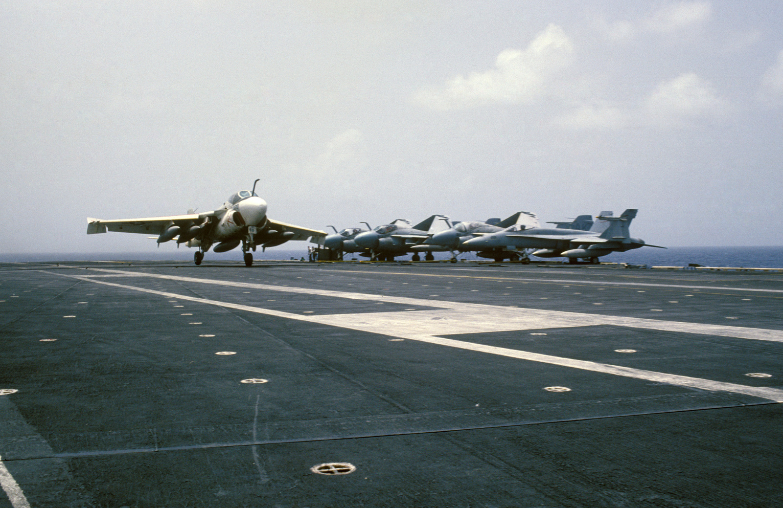 A KA-6D Intruder aircraft lands aboard the aircraft carrier USS CORAL SEA (CV 43). Parked at the deck edge are several A-6E Intruders and an F/A-18A Hornet aircraft