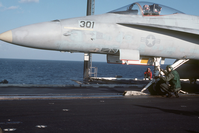 Catapult crewmen attach an F/A-18A Hornet aircraft to a catapult during flight operations aboard the aircraft carrier USS CORAL SEA (CV 43)