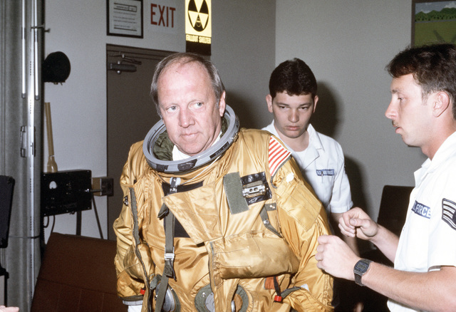 SENIOR AIRMAN (SRA) Darren A. Phillips and STAFF Sergeant (SSGT) Allan A. Whitacre check the fit of the flight suit worn by Representative Robert E. Badham, Republican-California, during the official's visit to the Physiological Support Branch.  Badham is