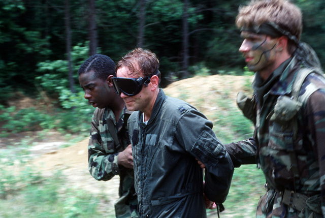 """AIRMAN First Class (A1C) Kevin Turner and SENIOR AIRMAN (SRA) Mark White lead Captain (CPT) Steven Sabourin away to a prisoner of war camp following his""""capture""""during a Strategic Air Command (SAC) combat survival training exercise"""