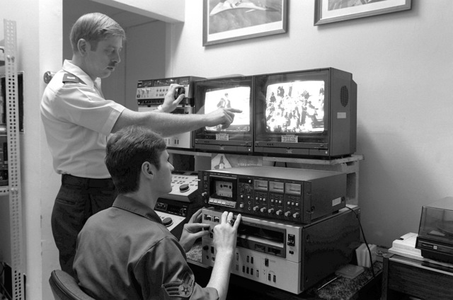MSGT Richard A. Mansfield, audiovisual manager for the 354th Combat Support Group, standing, explains the film editing machine to SGT Robert Roswell in the film library