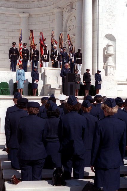 Chaplain (Brig. GEN.) John P. McDonough, deputy chief of chaplains, USAF, gives the invocation during the 1986 Military Nurse Memorial Service at Arlington National Cemetery. Standing on the platform are, left to right, Karen P. Keesling, principal deputy assistant secretary of the Air Force; Brig. GEN. Carmelita Schimmenti, chief of the Air Force Nurse Corps; Brig. GEN. Connie L. Slewitzke, chief of the Army Nurse Corps; Rear Adm. Mary J. Nielubowicz, chief of the Navy Nurse Corps; and CAPT. Virginia F. Connelly, moderator