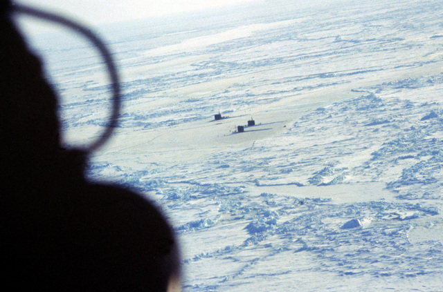 An elevated view of the attack submarines USS RAY (SSN-653), USS HAWKBILL (SSN-666), and USS ARCHERFISH (SSN-678) surfaced at the geographic North Pole. This is the first time three nuclear-powered submarines have simultaneously surfaced at the pole