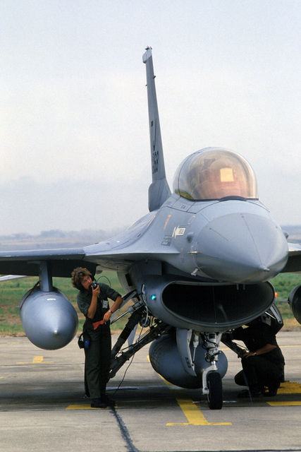 A crew chief goes through a preflight check on a 612th Tactical Fighter Squadron F-16B Fighting Falcon aircraft at the end of a runway