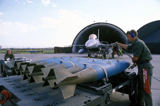 A weapons load crew chief from the 612th Tactical Fighter Squadron unstraps Mark-82 500-pound practice bombs, while another crew chief moves a bomb loader into position