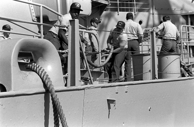 Crew members haul in morring lines as the battleship USS MISSOURI (BB-63) prepares to depart for San Francisco where it will be recommissioned