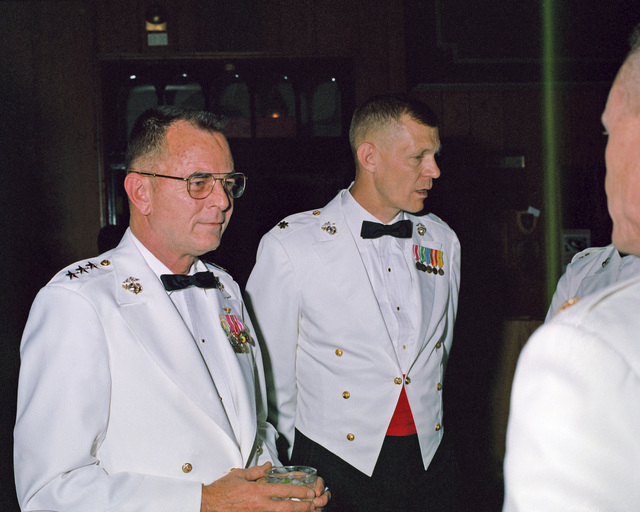 Lieutenant General (LGEN) Thomas R. Morgan, deputy chief of staff for plans, policy and operations, speaks with Major Okland during a Command and STAFF College mess night
