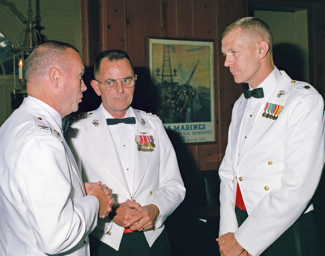 Lieutenant General (LGEN) Thomas R. Morgan, deputy chief of staff for plans, policy and operations, talks with Colonel (COL) Brown, left, and Major Okland during a Command and STAFF College mess night