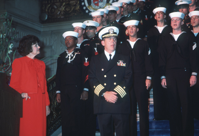 Captain (CAPT) Albert L. Kaiss, commanding officer of the battleship USS MISSOURI (BB 63), sings with members of his crew during a post-recommissioning ceremony at City Hall. On the left is Mayor Dianne Feinstein of San Francisco