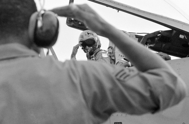 An airman salutes a pilot in the cockpit of an aircraft prior to the start of the Gunpowder '85 competition