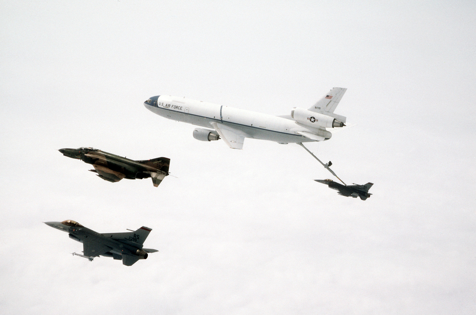 An F-16C Fighting Falcon and an F-4E Phantom II aircraft, both of the 526th Tactical Fighter Squadron (TFS) fly alongside as a KC-10A Extender aircraft refuels a 526th TFS F-15C. The F-4E aircraft of the 526th TFS are being replaced by the F-16C aircraft