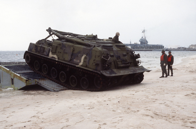 An M-88A1 armored recovery vehicle off-loads from a ribbon bridge during rapid response loading Exercise Agile Sword '86