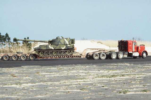 Civilian contracted trucks move military equipment to the training site during rapid response loading Exercise AGILE SWORD'86