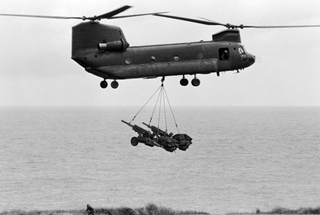 A CH-47 Chinook helicopter airlifts two M102 105 MM Howitzers of the 7th Battalion, 8th Field Artillery Regiment, during Exercise OPPORTUNE JOURNEY 2-86