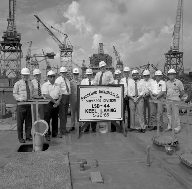 Caplt. P.D. Hurst, supervisor of shipbuilding, fifth from the left, poses with employees of Avondale Industries, Inc. during the keel laying of the Whidbey Island class dock landing ship LSD-44. In the background a fleet oiler is under construction