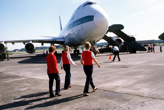 Red Coat volunteers walk out to greet military personnel and their families arriving on a commercial Boeing 747 aircraft. The Red Coats are passenger service volunteers from the Yokota Officers' Wives Club. They assist regular terminal workers by greeting new arrivals and guiding them through terminal processing and customs procedures