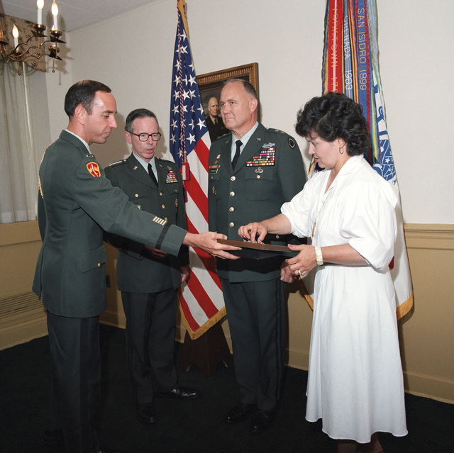 Mrs. Brenda Schwarzkopf picks up a three-star rank insignia from a case offered by CHIEF Warrant Officer 3 John L. Drummond, left, as she and General Maxwell R. Thurman, second from left, Vice CHIEF of STAFF, US Army, prepare to pin the stars on the shoulders of Lieutenant General H. Norman Schwarzkopf during his promotion ceremony at the Pentagon