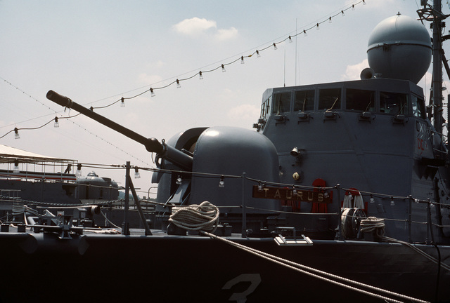 A view of the Mark 75 76 mm/62-caliber gun on the bow of the patrol missile hydrofoil USS TAURUS (PHM 3). The vessel is moored at pier No. 2 at the Washington Navy Yard