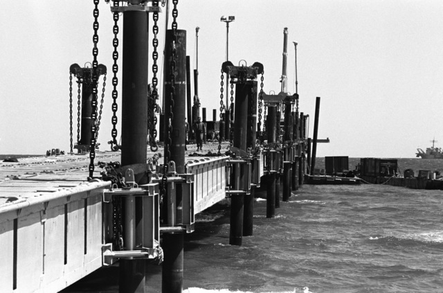 A barge ties up to a pier constructed by members of Amphibious Construction Battalion 2 during Exercise ELCAS (ELEVATED CAUSEWAY), a training exercise in which Seabees learn pier-construction techniques