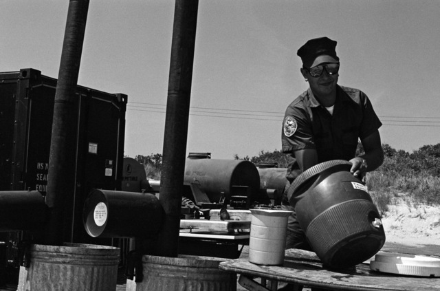 A cook with Amphibious Construction Battalion 2 cleans a soft drink container during Exercise ELCAS (ELEVATED CAUSEWAY), a training exercise in which Seabees learn pier-construction techniques