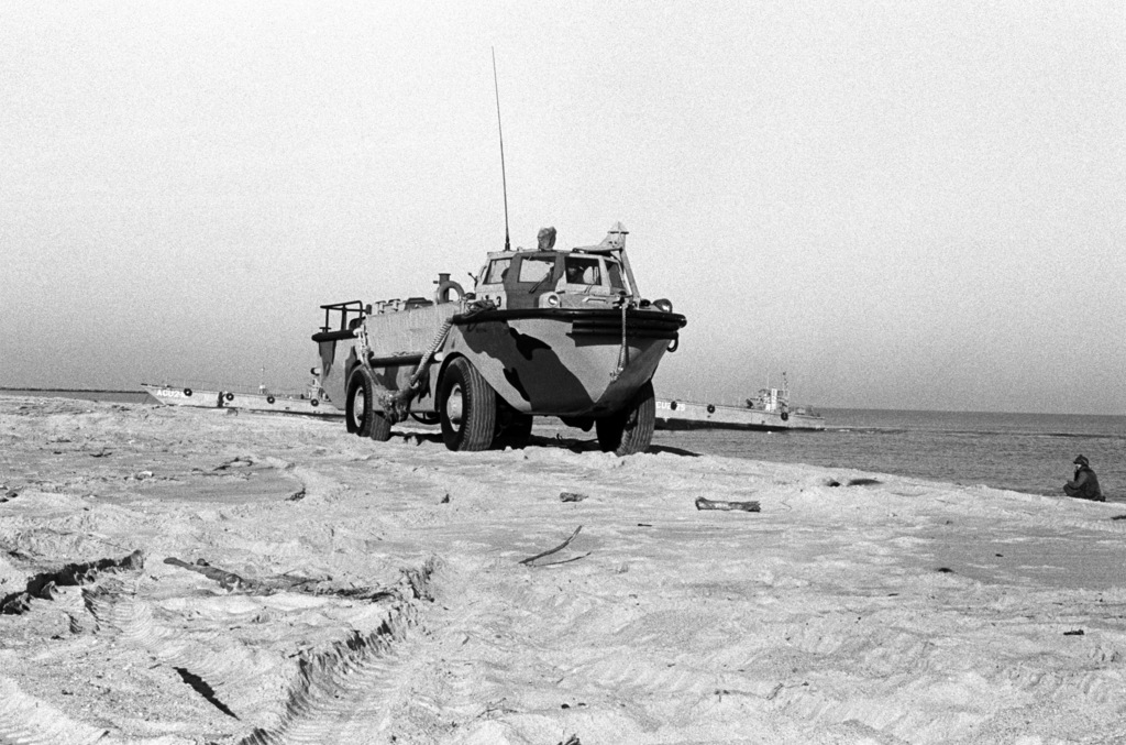 A LARC 5 amphibious cargo carrier travels along the beach. A pier constructed by Amphibious Construction Battalion 2 during Exercise ELCAS (ELEVATED CAUSEWAY), a training exercise in which Seabees learn pier-construction techniques, is visible in the background