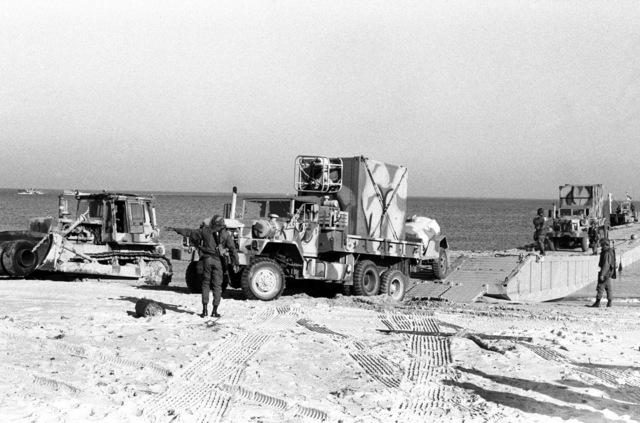 A member of Amphibious Construction Battalion 2 directs the movement of equipment from a causeway into the beach during Exercise ELCAS (ELEVATED CAUSEWAY), a training exercise in which Seabees learn pier-construction techniques