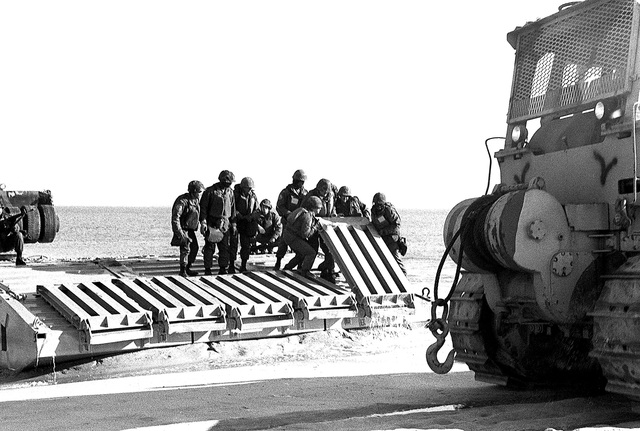 Members of Amphibious Construction Battalion 2 lift sections of a causeway during Exercise ELCAS (Elevated Causeway), a training exercise in which Seabees learn pier-construction techniques