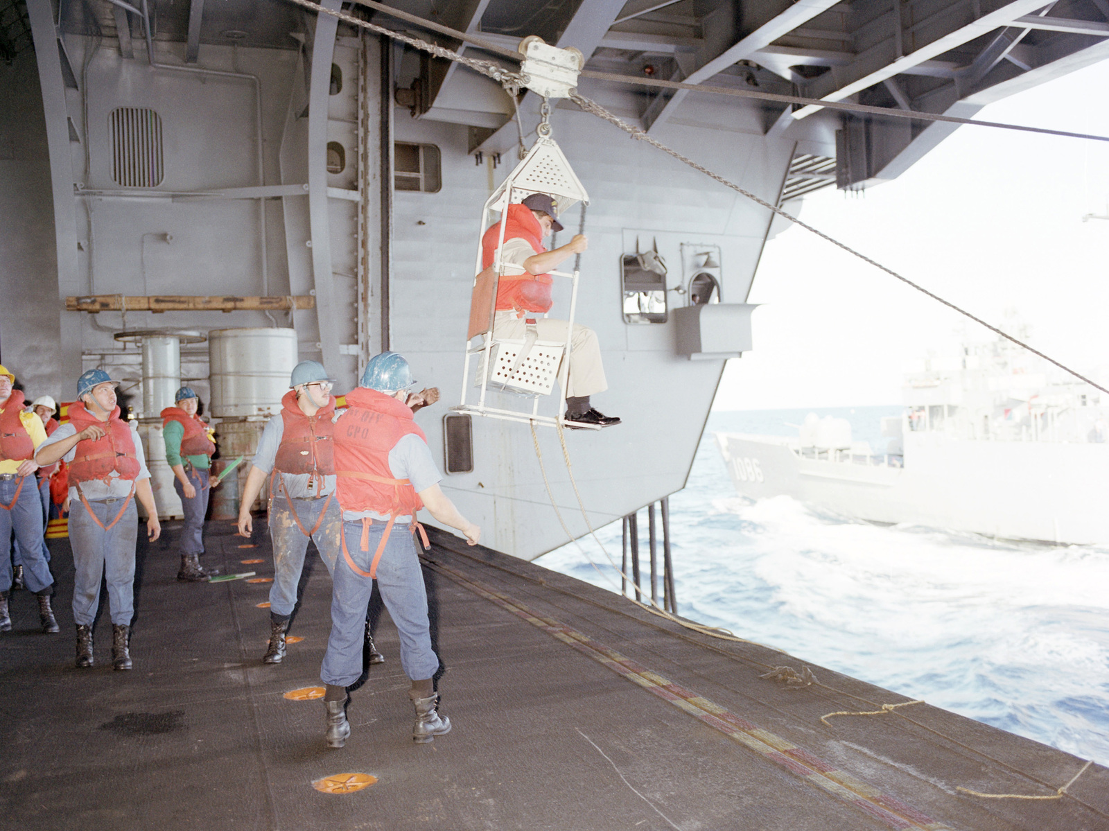 A transfer chair and highline are used to transport an officer from the nuclear-powered aircraft carrier USS CARL VINSON (CVN 70) to the frigate USS BREWTON (FF 1086) during an underway replenishment