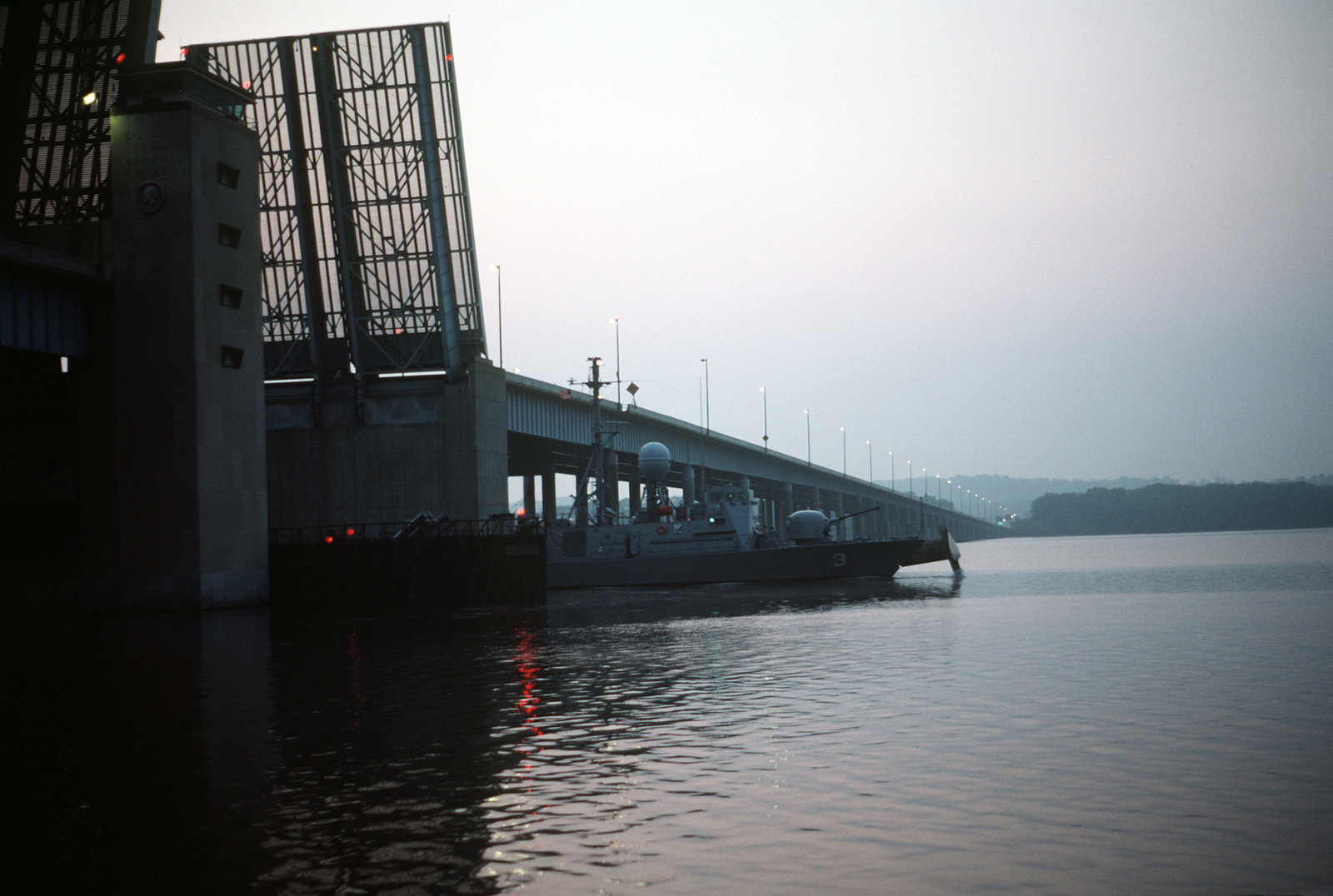 The patrol missile hydrofoil USS TAURUS (PHM 3) passes through the open draw span of the Woodrow Wilson Memorial Bridge on the Potomac River