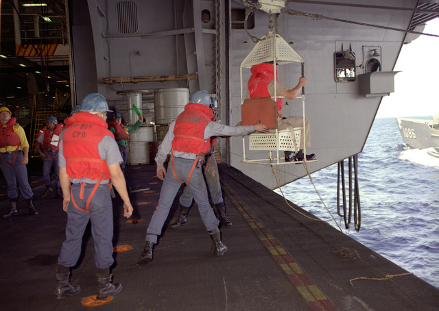 A transfer-at-sea chair on a highline rig is used to return a crewmember from the nuclear-powered aircraft carrier USS CARL VINSON (CVN-70) to the frigate USS BREWTON (FF-1086) during an underway replenishment