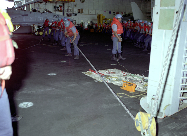 Crew members haul on a line while using a transfer-at-sea chair to transport personnel from the nuclear-powered aircraft carrier USS CARL VINSON (CVN-70) to the frigate USS BREWTON (FFG-1086)